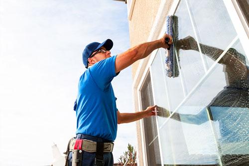 Mann reinigt Glas und Fensterrahmen